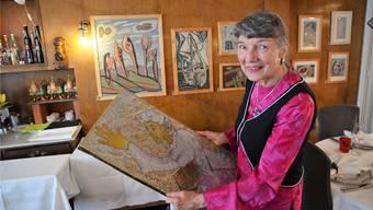 Helene Muntwyler zeigt ein preisgekröntes Werk von ihr, im Hintergrund Werke ihres Schwiegervaters Hermann Arnold Muntwyler. ES
