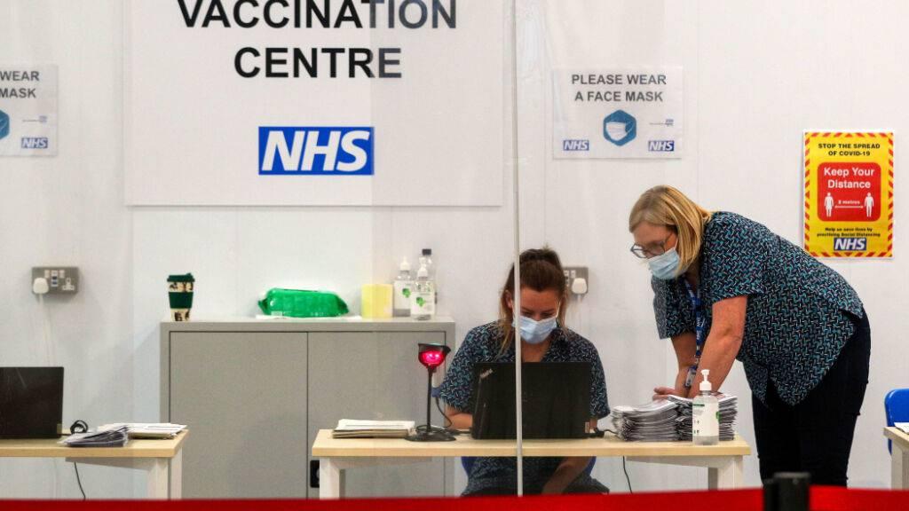 ARCHIV - Mitarbeiterinnen arbeiten in einem Impfzentrum in der Kathedrale von Blackburn, im HIntergrund das Logo des Nationalen Gesundheitsdiensts NHS. Foto: Peter Byrne/PA Wire/dpa