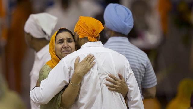 Zwei Sikhs umarmen sich bei der Trauerfeier in Oak Creek