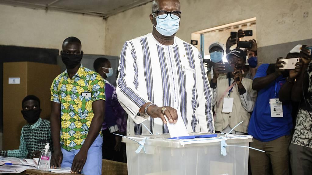 ARCHIV - Burkina Fasos Präsident Roch Kabore gibt seinen Stimmzettel bei den Präsidentschaftswahlen im November letzten Jahres ab. Nachdem mehr als 100 Menschen bei einem bewaffneten Überfall getötet wurden, hat er eine dreitägige Staatstrauer angeordnet. Foto: Sophie Garcia/AP/dpa