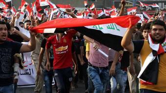 Iraker mit Nationalflaggen bei ihrer Kundgebung in Bagdad