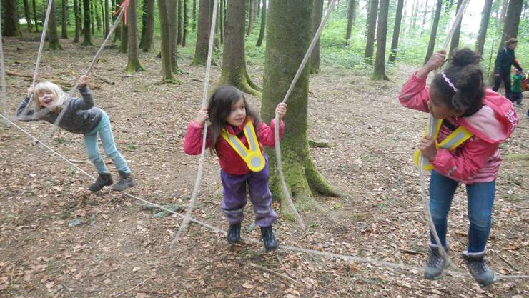Die Kindergärtler sammeln Bewegungsminuten auf dem Kletterpark im Wald.