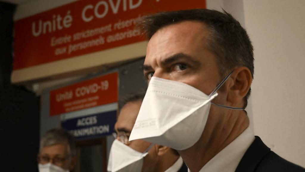 Olivier Veran, Gesundheitsminister von Frankreich, spricht mit medizinischen Mitarbeitern während eines Besuchs eines öffentlichen Krankenhauses. Foto: Christophe Simon/POOL AFP/AP/dpa