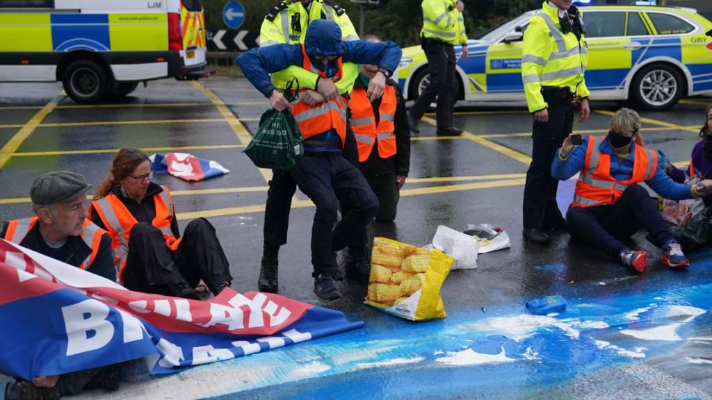 Polizisten nehmen Aktivisten der Organisation «Insulate Britain» auf einer Londoner Autobahn fest. Foto: Steve Parsons/PA Wire/dpa