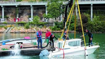 Leeren: Seepolizeichef Fritz Brünisholz (r.) und seine Kollegen pumpen das Wasser aus dem geborgenen Motorboot. (uz)