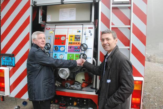 Paul Meyer links Gemeindeamman villmergen und Norbert Kräuchi Leiter Abteilung Landschaft und Gewässer drehen beim Tanklöschfahrzeug der Feuerwehr den Wasserhahn für die Einweihung auf.