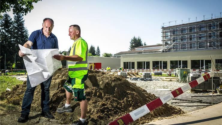 Unter Zeitdruck wird bei der Primarschule Rüsler ein Pavillon gebaut. Bauverwalter Sandro Fischer (l.) und Polier Frank Brogle besprechen die nächsten Schritte. Cris Iseli
