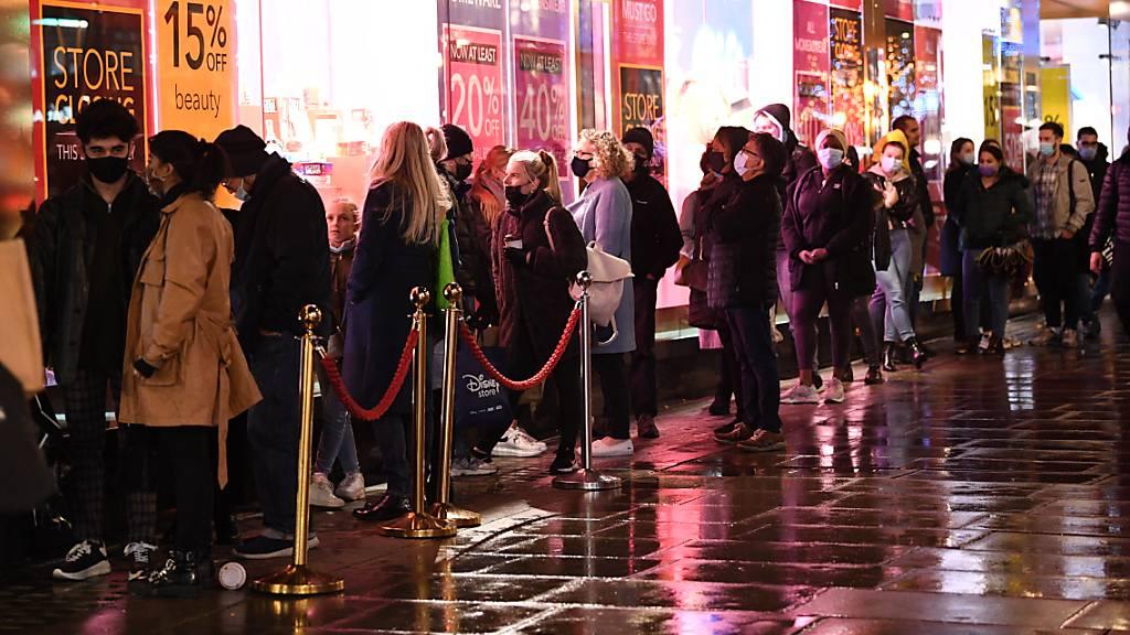 Menschen stehen am letzten Samstag vor Weihnachten auf der Oxford Street in London vor einem Geschäft Schlange.