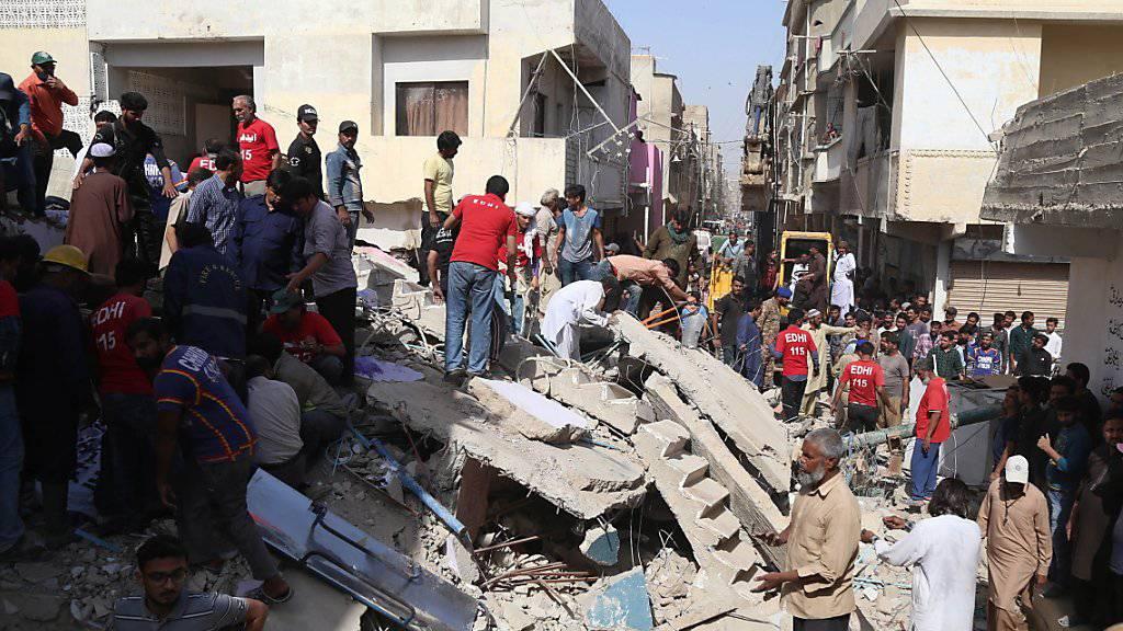 Nach dem Einsturz eines Wohnhauses in der pakistanischen Hauptstadt Karachi suchen Rettungskräfte nach Opfern.