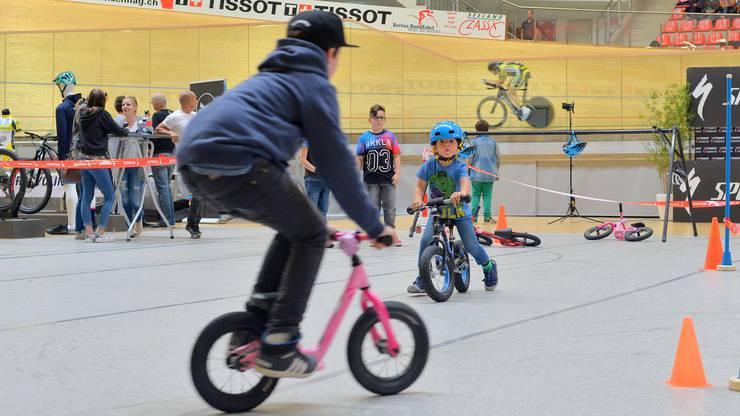 Die Kids vergnügen sich im Velodrome, während im Hintergrund Christoph Strasser seine Runden dreht.