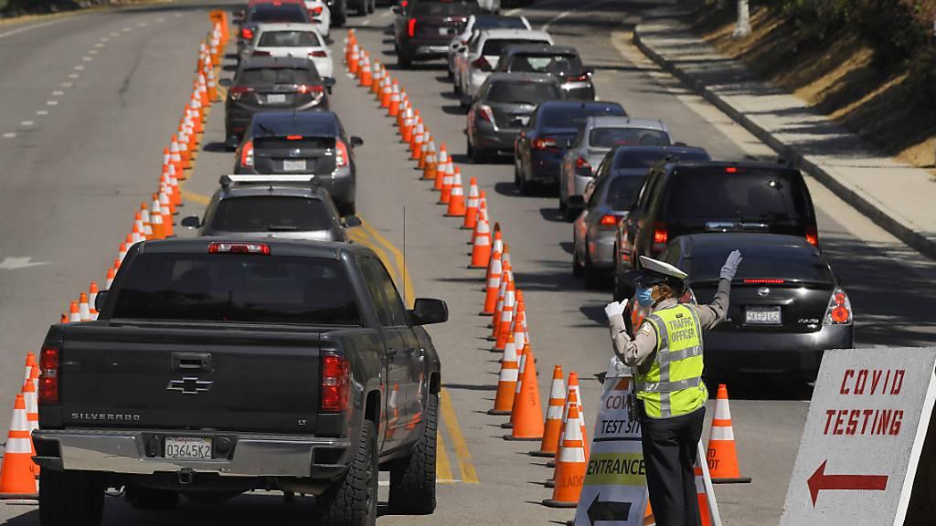 Fahrzeuge stehen vor dem Dodger Stadium in Los Angeles für einen Coronavirus-Test in einer Schlange. Foto: Mark J. Terrill/AP/dpa
