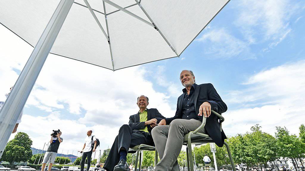 Endlich: Die Zürcher Stadträte Richard Wolff (links) und Filippo Leutenegger (rechts) können auf dem Sechseläutenplatz unter einem robusten Sonnenschirm den Schatten geniessen. Das Vorgängermodell war vom Winde verweht und zerzaust worden.