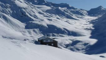 In der verschneiten Landschaft steht die Maighels-Hütte.