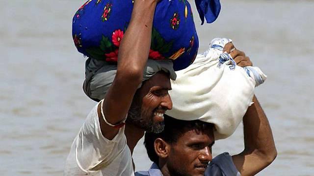 Zwei Männer tragen in Pakistan ihr Hab und Gut durch die Fluten