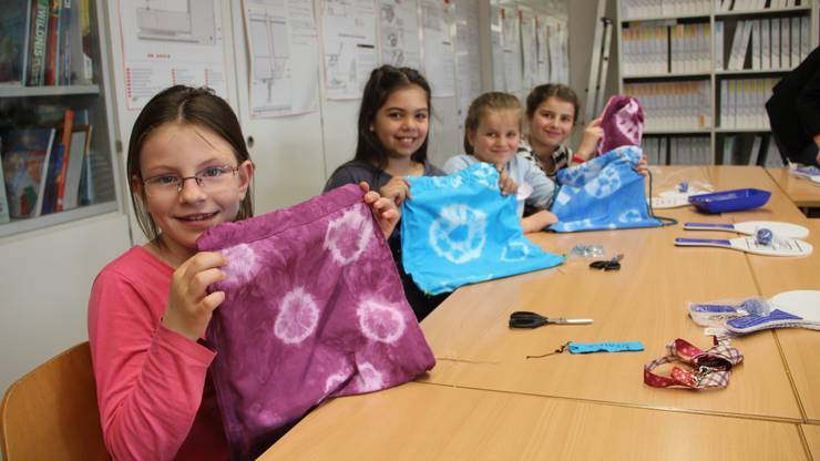 Simone (8), Beatriz (10), Elena (9) und Muriel (10) zeigen ihre selbstgefärbten und -genähten Beutel.