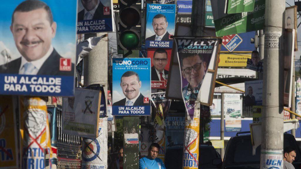 Ein Bewohner von Guatemala-Stadt inmitten zahlreicher Wahlplakate.
