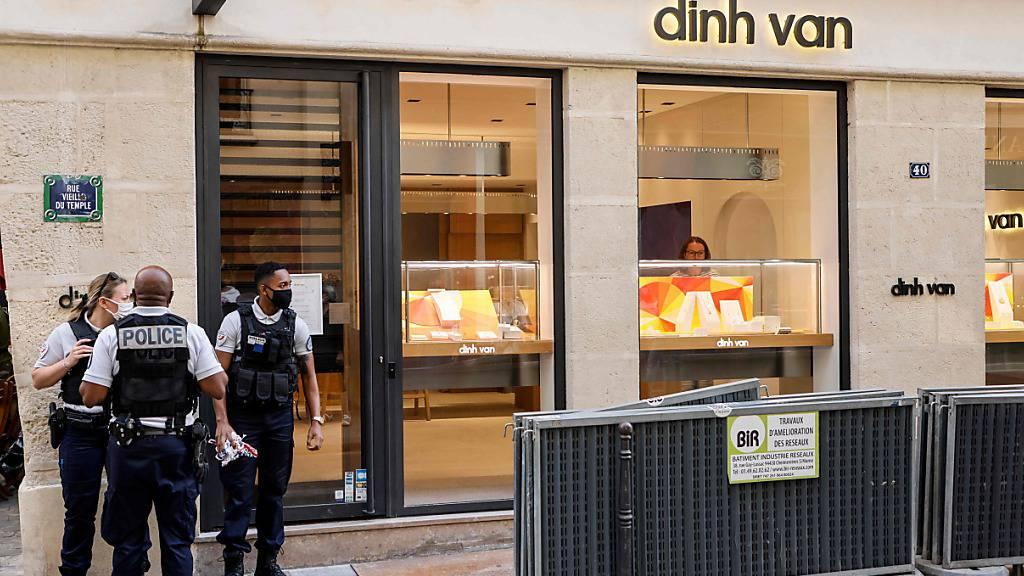 Französische Polizeibeamte stehen nach einem Raubüberfall auf ein Juweliergeschäft vor dem Gebäude. In Paris haben zwei Menschen einen Juwelierladen überfallen und Schmuck und Bargeld geraubt. Foto: Ludovic Marin/AFP/dpa