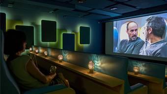 Der Saal drei im neuen Kult Kino Atelier bietet Bänke mit beleuchteten Tischchen.
