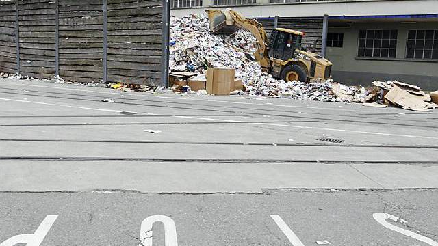 Ein Bagger schiebt Papier und Karton in die Sammelstelle beim Fabriksgebäude der Firma Karton Deisswil (Archiv)