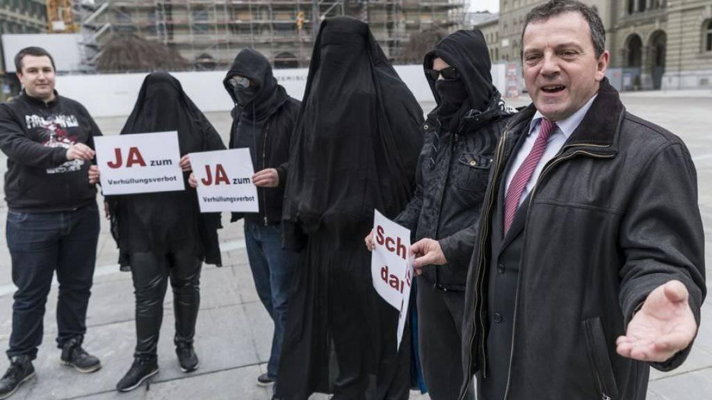 SVP-Nationalrat Walter Wobmann (r.) und der ehemalige Präsident der Jungen SVP, Anian Liebrand, (l.) posieren auf dem Bundesplatz in Bern mit als Burkaträgerinnen und Hooligans verkleideten Komiteemitgliedern.
