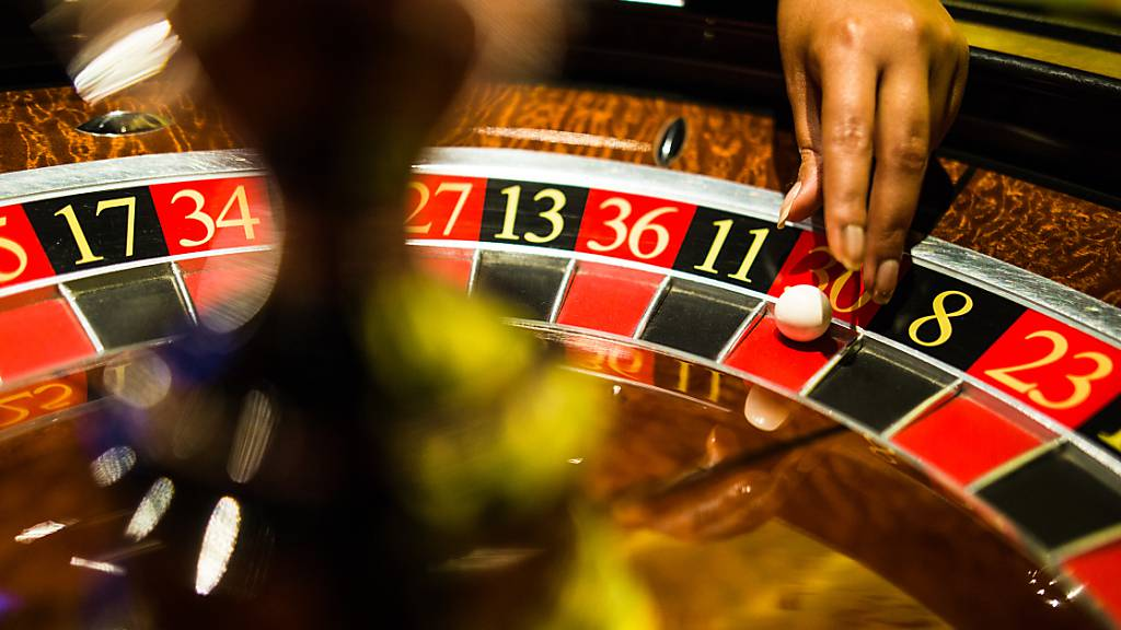 Eine Mitarbeiterin der Spielbank Stuttgart greift beim Spiel Roulette nach einer Kugel, die auf Rot liegt.