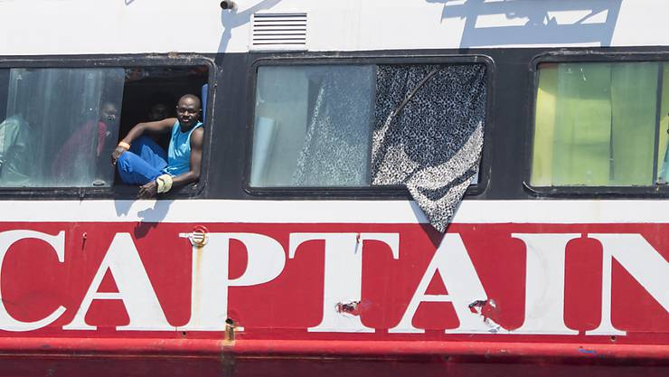 dpatopbilder - Migranten blicken aus dem Fenster an Bord eines Touristenbootes etwa 20 Kilometer vor Malta. Foto: Rene' Rossignaud/AP/dpa