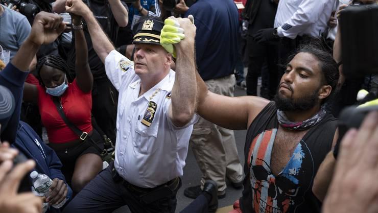 Terence Monahan, Chief of Department der New York Police, kniet zusammen mit Aktivisten nieder.