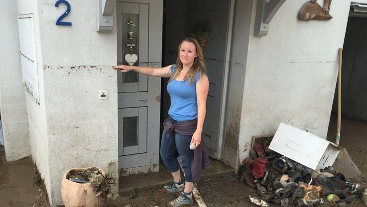 «So hoch stand das Wasser.» Rebecca Kaiser im Eingangsbereich des Hauses ihrer Eltern. Vor und neben ihr Habseligkeiten, die total durchnässt und verdreckt wurden. Fast alles muss weggeworfen werden.