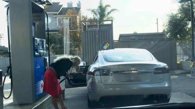 Blondine will Elektroauto mit Benzin tanken