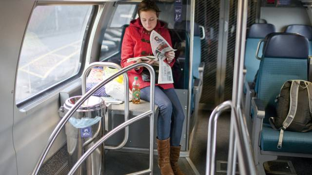 Eine junge Frau liest im Zug eine Pendlerzeitung (Archiv)