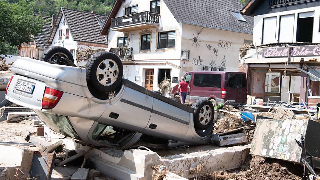 Ein von der Flut mitgerissenes Auto liegt in der Stadtmitte von Altenahr in Rheinland-Pfalz. Foto: Boris Roessler/dpa