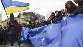Menschen gehen mit Europa-Fahnen auf die Strasse