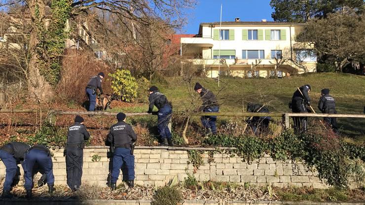 Das Gelände um den Tatort, insbesondere das teil unbebaute Nachbargrundstück, wird grossräumig abgesucht.