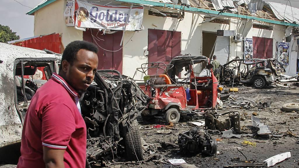 Ein Mann geht an Wrackteilen am Tatort eines Bombenanschlags vorbei. Nach Angaben der Polizei starben ein Selbstmordattentäter und mehrere Zivilisten wurden verwundet, als ein Fahrzeug in der Nähe eines Kontrollpunkts vor dem Präsidentenpalast in Somalias Hauptstadt Mogadischu explodierte. Foto: Farah Abdi Warsameh/AP/dpa