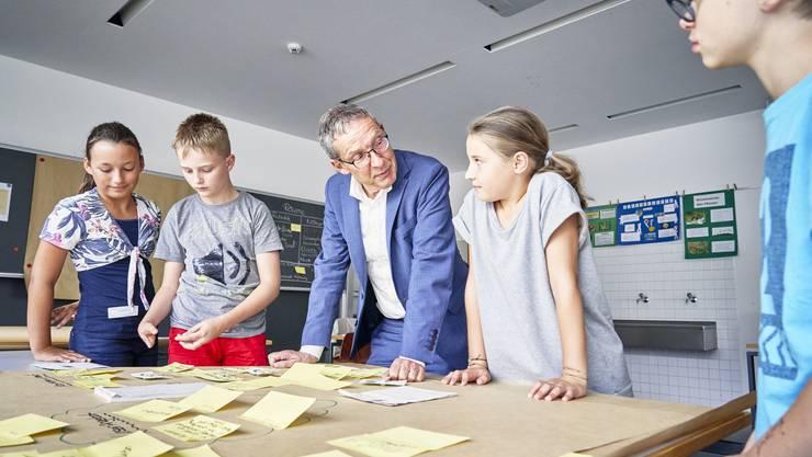 Die Schüler erklären Landammann Urs Hofmann, wie sie sich ihr Roboter-Restaurant vorstellen.