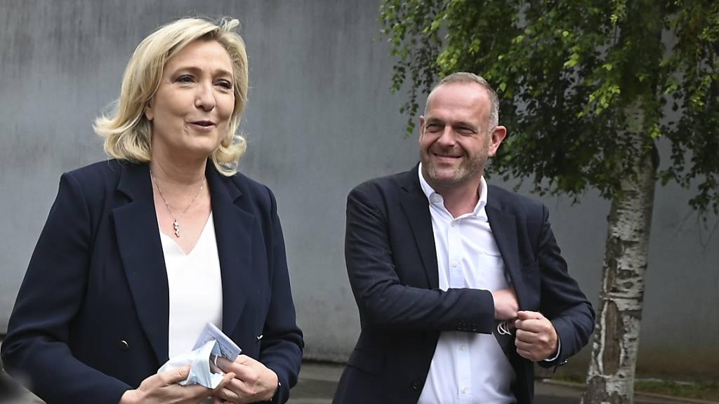 Marine Le Pen, Parteivorsitzende der Rassemblement National,  und der lokale Kandidat Steeve Briois gehen nach der Stimmabgabe bei den Regionalwahlen. Foto: Uncredited/AP/dpa