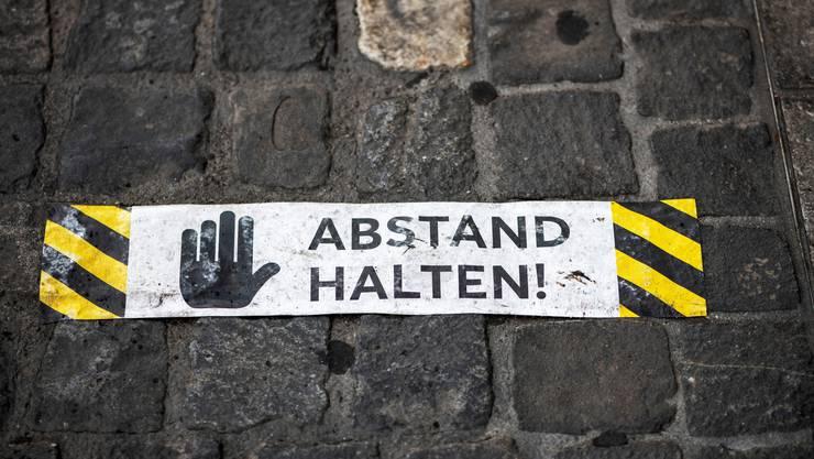 Schutzmassnahme: Eine Bodenmarkierung in Zürich ermahnt die Menschen vor einem Geschäft Abstand zu halten.