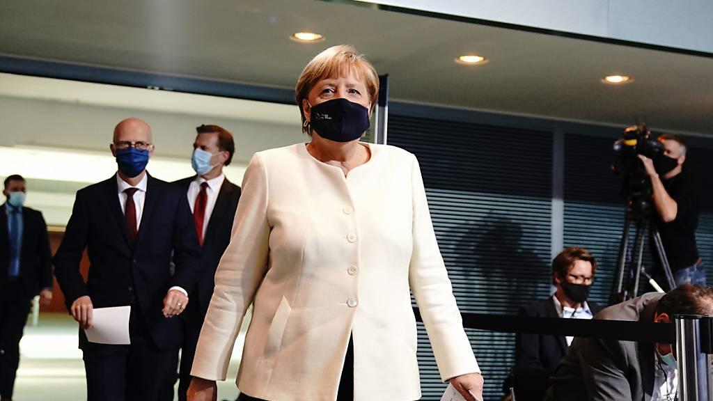 Bundeskanzlerin Angela Merkel (CDU) und Peter Tschentscher (SPD -2.v.l.), Erster Bürgermeister von Hamburg, kommen zur Pressekonferenz. Foto: Kay Nietfeld/dpa