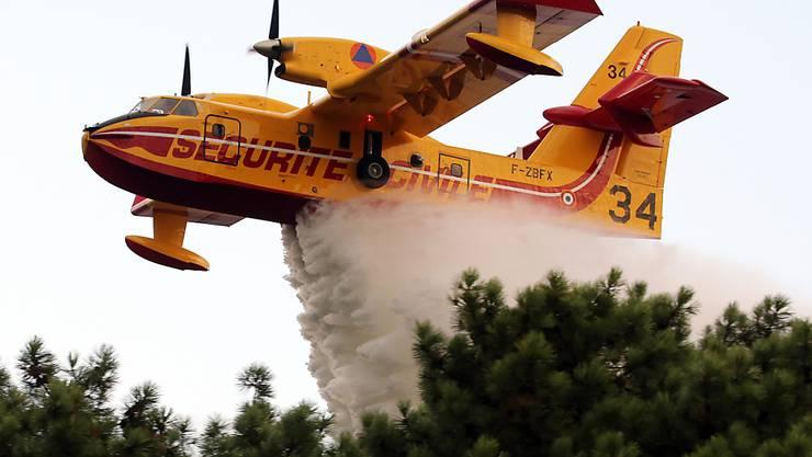 Ein Löschflugzeug ist bei einem Waldbrand im Südwesten Frankreichs im Einsatz. Wegen eines Waldbrands in Südfrankreich haben zahlreiche Menschen ihre Häuser verlassen müssen. Foto: Bob Edme/AP/dpa
