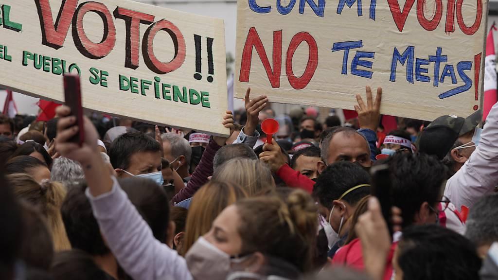 Unterstützer der Präsidentschaftskandidatin Fujimori protestieren gegen angeblichen Wahlbetrug vor der Stelle der Stimmauszählung. Foto: Martin Mejia/AP/dpa