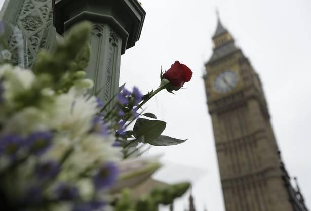 Blumengaben in gedenken an die Opfer des Attentats dominieren die Szenerie um das Westminster.