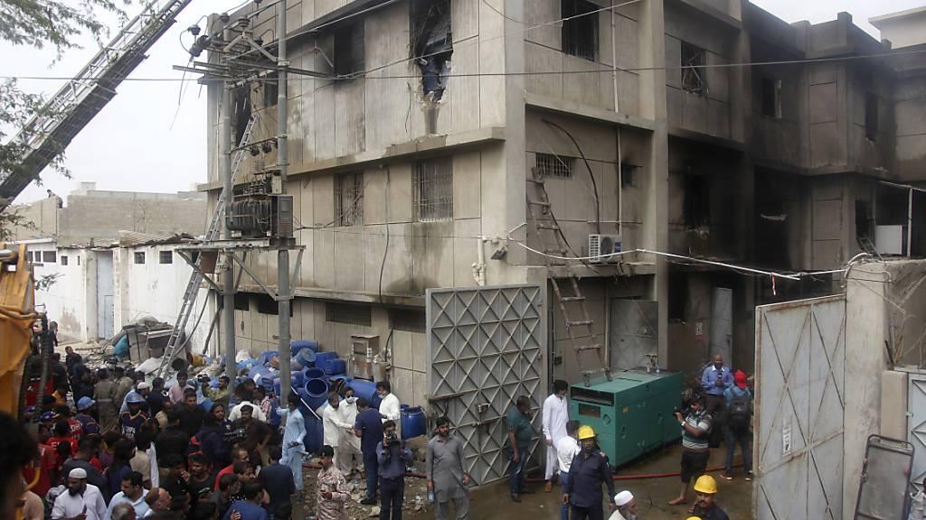 Rettungskräfte suchen nach Leichen in einer abgebrannten Chemiefabrik. Bei einem Brand in einer Chemiefabrik sind mindestens 15 Menschen gestorben. Der Einsatz in dem teilweise eingestürzten Gebäude dauere noch an. Das Feuer sei durch eine hochentzündliche Chemikalie ausgelöst worden. Foto: Ikram Suri/AP/dpa