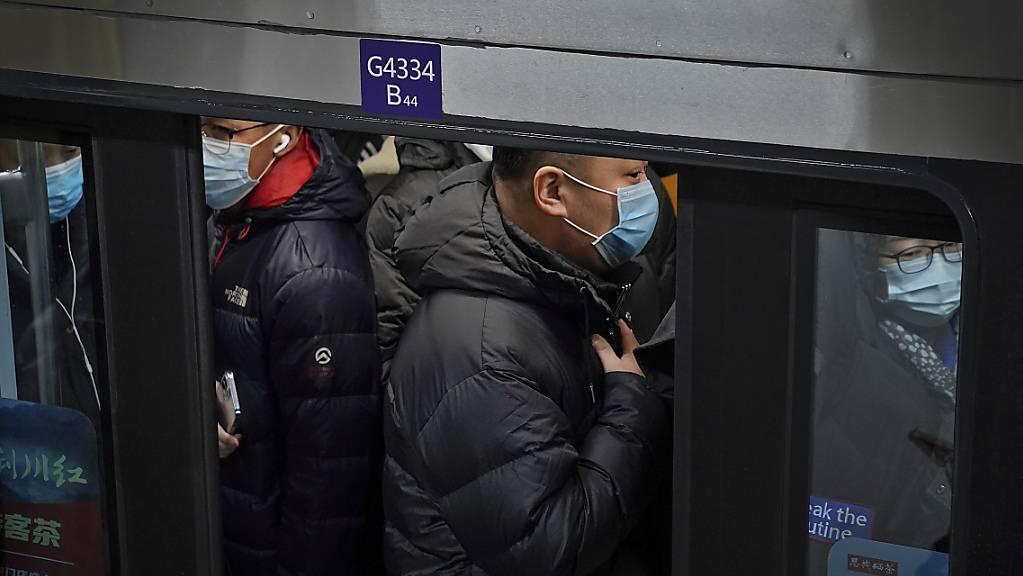 dpatopbilder - Pendler in Peking drängen sich in eine U-Bahn während der Hauptverkehrszeit. Foto: Andy Wong/AP/dpa