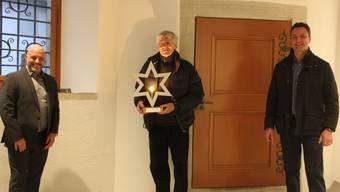 Cuno Jent, der Gestalter der neuen Weihnachtsbeleuchtung in Brugg, erhält als Dank für seine ehrenamtliche Arbeit im Stadtmuseum Geschenke von Dietrich Berger (l.), Präsident des Gewerbevereins Brugg, und von FDP-Stadtrat Reto Wettstein.
