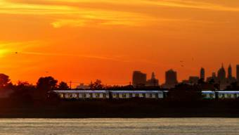 Ein Zug durchquert bei Sonnenuntergang die New Yorker Jamaica Bay. Im Hintergrund ragen die Wolkenkratzer von Manhattan in den Abendhimmel. New Yorks Bürgermeister Bill de Blasio will mit einer unorthodoxen Austernzucht die Wasserqualität des Feuchtgebiets verbessern. (Archiv)