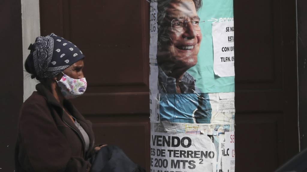 Eine Frau geht an einem Wahlplakat des Präsidentschaftskandidaten Lasso vorbei. Foto: Dolores Ochoa/AP/dpa