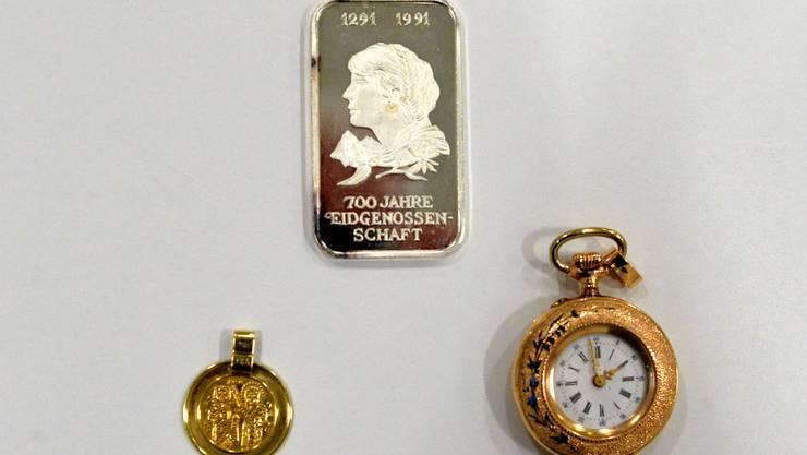 Silberbarren, goldene Anhänger und Taschenuhren befinden sich unter den konfiszierten Gegenständen.