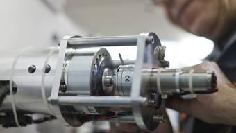 Ein Mitarbeiter der Georg Fischer kalibriert ein Motorenkabel. (Archiv)