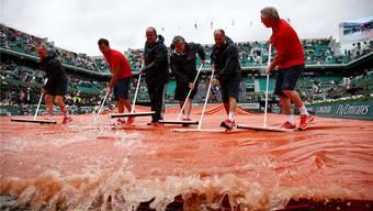 Helfer befreien die Abdeckung auf dem Court Philippe Chatrier vom Regenwasser – solche Probleme gäbe es mit einem Regendach nicht.