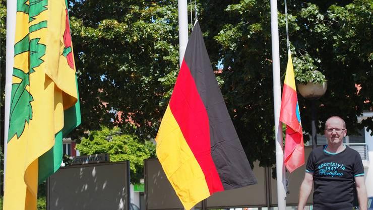 Gemeindeschreiber Markus von Däniken zieht für die «Schweiz am Sonntag» eine von der Stadt Olten geliehene Deutschland-Fahne auf (links die Fahne Lostorfs, rechts die der deutschen Partnergemeinde Rielasingen).